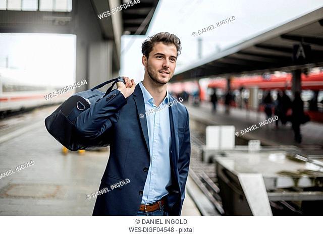 Smiling businessman with bag at the platform