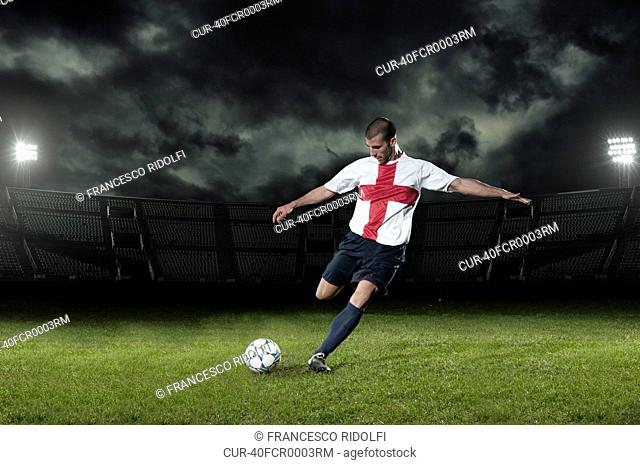Soccer player kicking ball in pitch