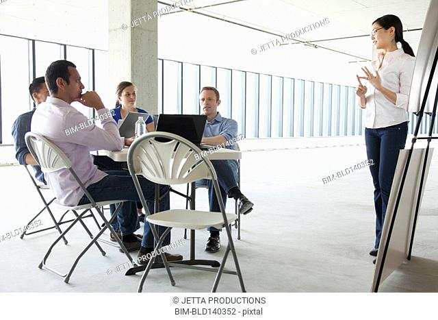 Businesswoman making presentation to colleagues