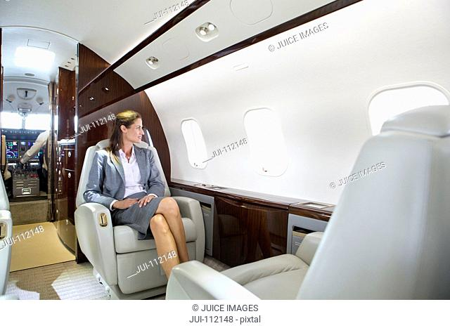 Businesswoman looking out of window on private jet