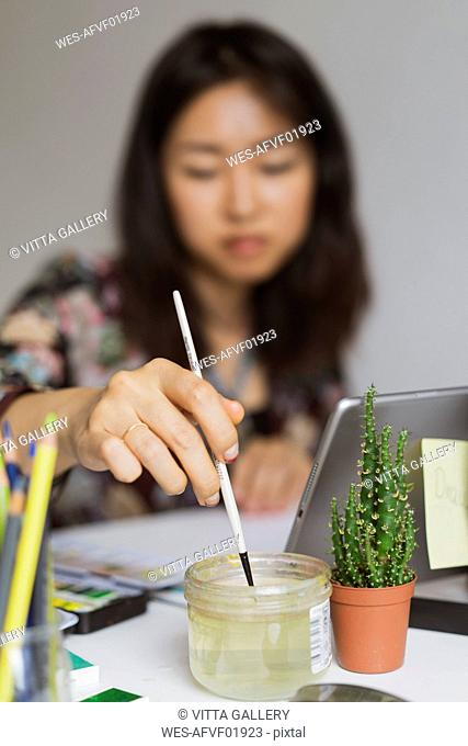 Illustrator painting at work desk in an atelier, close-up
