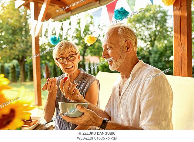 Senior couple eating tomatoes on a garden party
