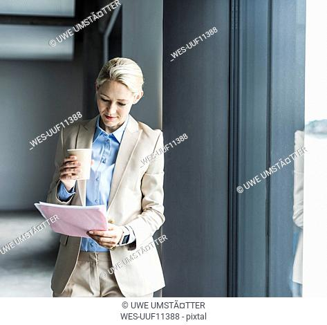 Businesswoman with coffee reading document at the window