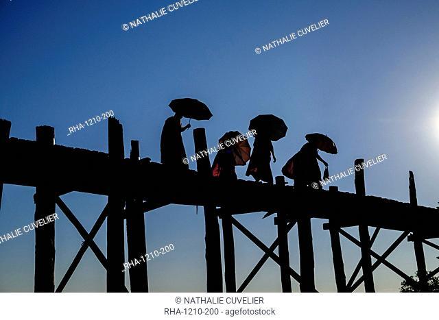 Buddhist monks silhouetted on the U Bein Bridge, Taungthman Lake, U Bein, Amarapura, Myanmar (Burma), Asia