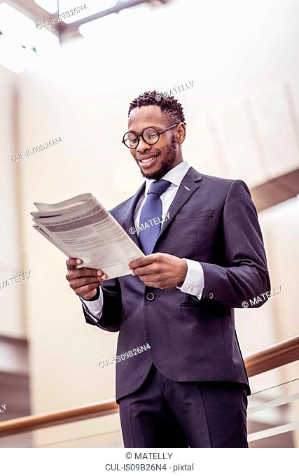 Businessman reading newspaper on office balcony