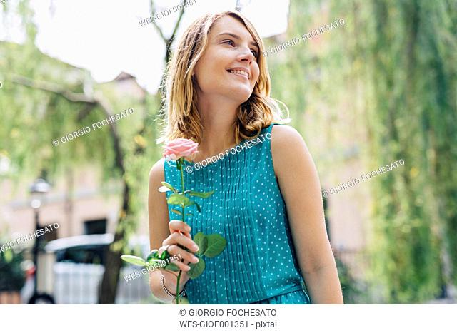 Smiling young woman with rose blossom