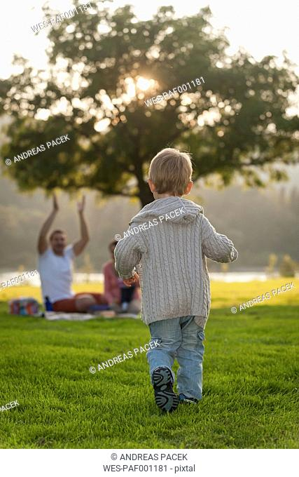 Boy running on meadow towards family in background