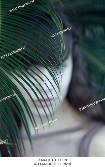 Woman hiding behind palm leaf