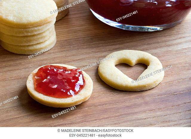Preparation of traditional Linzer Christmas cookies - filling the cookies with strawberry jam
