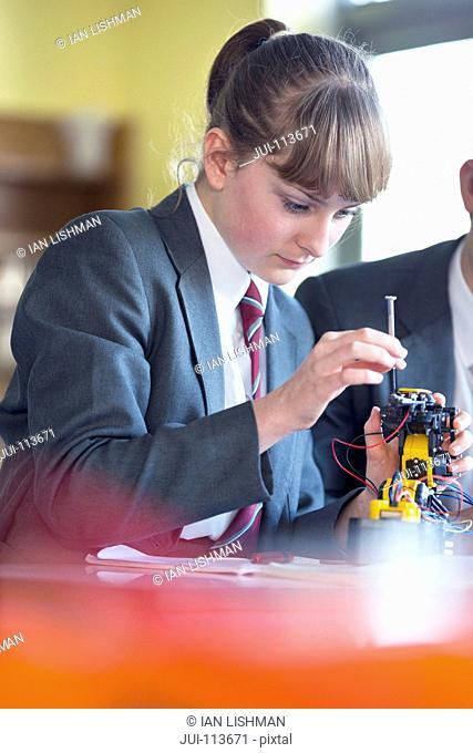 High school student assembling robot in science class