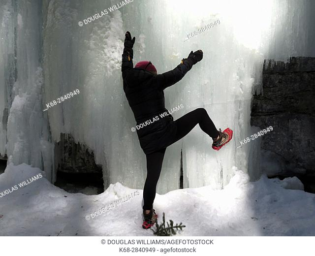 Woman and frozen waterfall in Maligne Canyon, Jasper, Alberta, Canada in winter