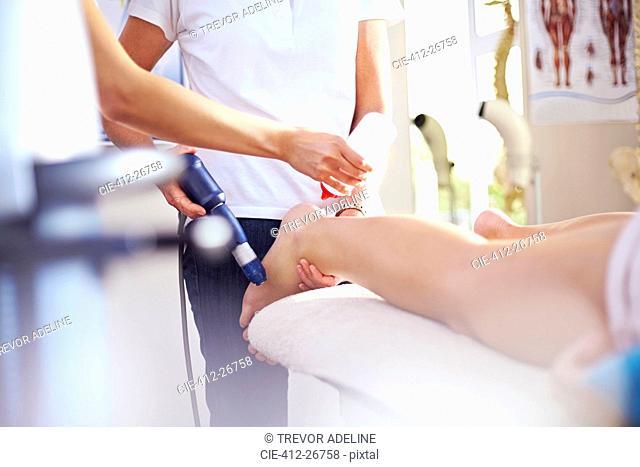 Masseuse applying gel to woman's leg in preparation for ultrasound probe
