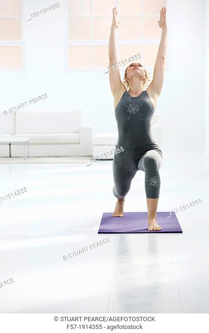 Healthy young woman doing the high lunge pose yoga position