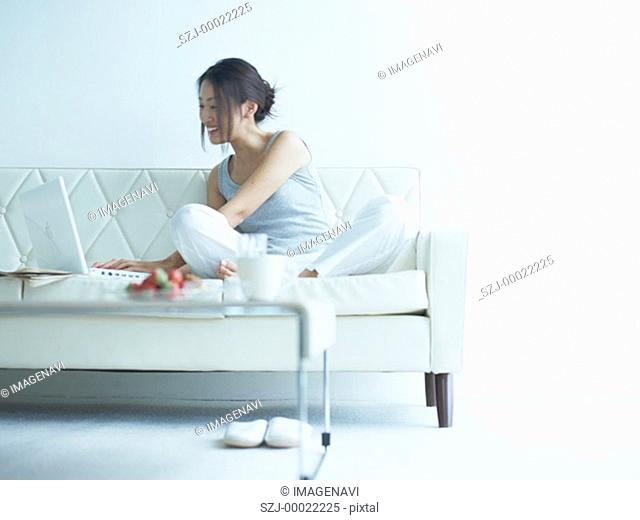 A smiling woman using laptop on sofa
