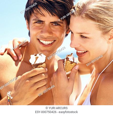 Closeup portrait of a young couple indulging in an ice cream