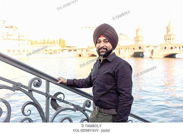 Indian man exploring city, river in background, Berlin, Germany
