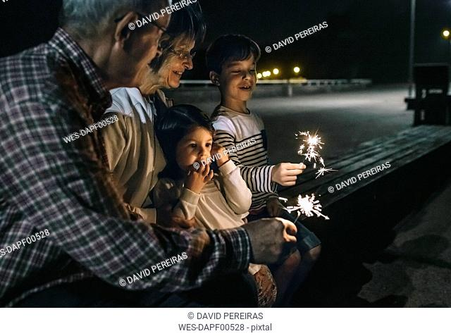 Grandparents with grandchildren holding sparklers at night