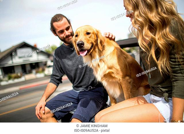 Young couple with dog sitting in back of jeep