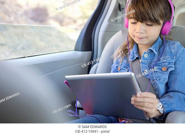 Girl with headphones using digital tablet in back seat of car