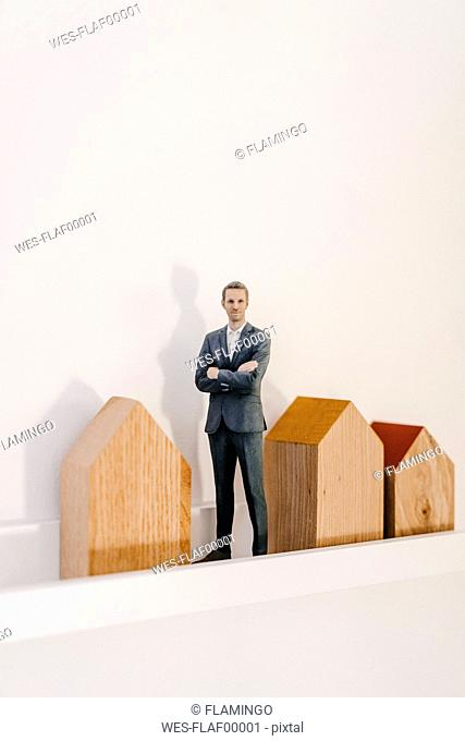 Businessman figurine standing by wooden house models