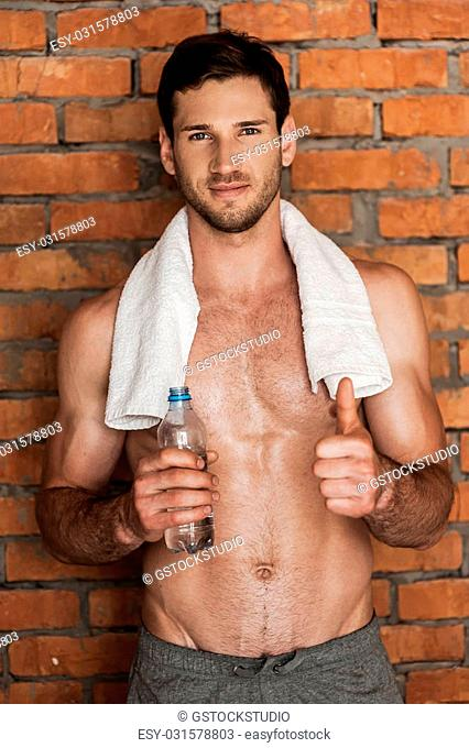 Perfect choice after good training! Smiling young muscular man with towel on shoulders holding a bottle with water and thumb up while standing against brick...