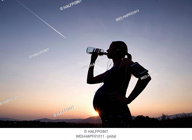 Silhouette of pregnant woman drinking water from bottle at sunset