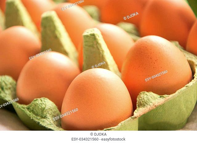 Some eggs in green cartone close up diagonal perspective