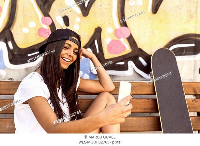 Smiling young woman with skateboard looking at cell phone