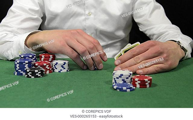 Poker player looking at his cards, fiddling contemplative with his chips, and going all-in