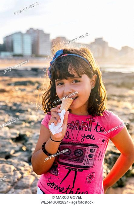 Portrait of smiling little girl eating icecream on the beach at sunset