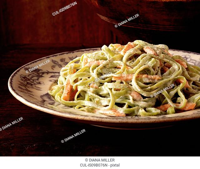 Spaghetti with creamy sauce and salmon on vintage plate