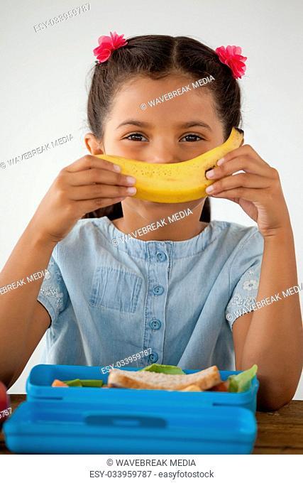 Schoolgirl having breakfast against white background