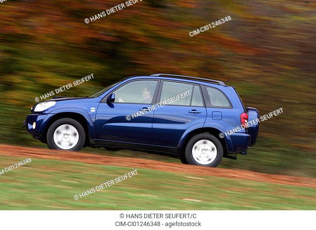Car, Toyota RAV4 D-4D, cross country vehicle, model year 2004-, blue moving, side view, country road, Herbst, Foliage