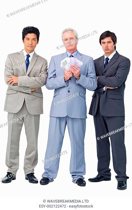 Senior salesman with money and his employees against a white background