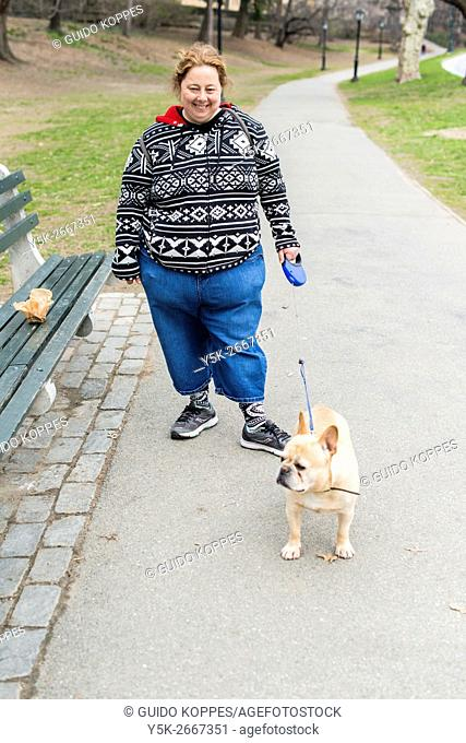 New York City, USA. Female, caucasian dogwalker, walking the dog of one of her customer's through Central Park, Manhattan
