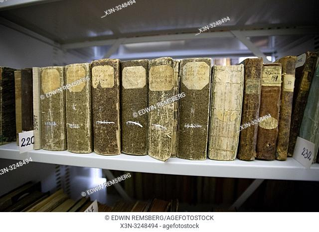 Close shot of a series of older and worn Polish books sitting on a shelf in a library. Central Agricultural Library, Warsaw, Masovian Voivodeship, Poland