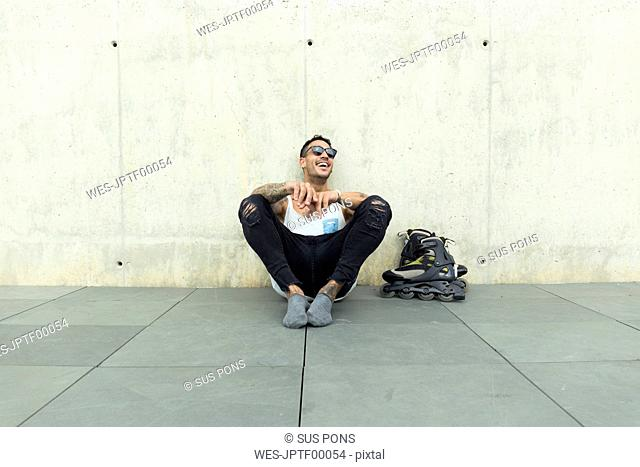 Tattooed young man with roller skates sitting on ground having fun