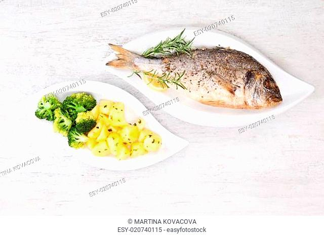 Grilled sea bream with potatoes on plate