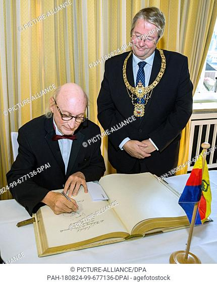24 August 2018, Germany, Emden: Comedian and musician Otto Waalkes (l) has been granted honorary citizenship of the city of Emden and signs the city's Golden...