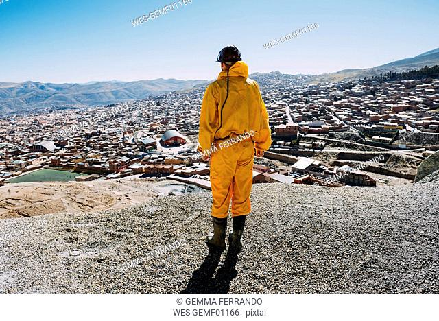 Bolivia, Potosi, back view of tourist wearing protective clothing looking to the city