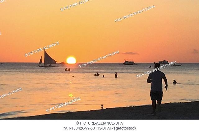 24 April 2018, Philippines, Boracay Island: Tourists strolling on the beach at sunset. A few weeks ago the island was still a dream goal