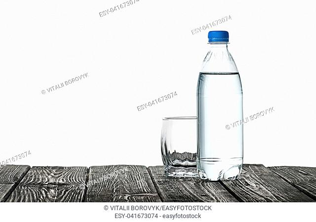 Empty glass and bottle of water. Plastic bottle on a wooden table. Isolated on white background
