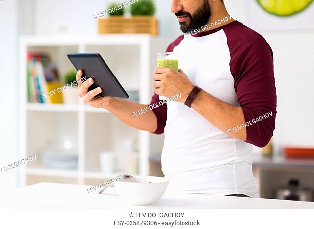 healthy eating, people, technology and diet concept - man with tablet pc computer and smoothie having breakfast at home kitchen