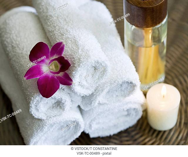 USA, California, Oakland, rolled up towels, aroma sticks, candle and orchid on table