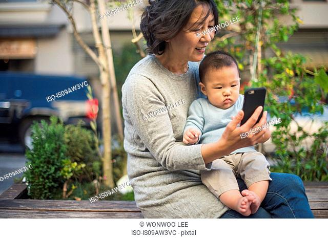 Grandmother showing smartphone to grandson outdoors