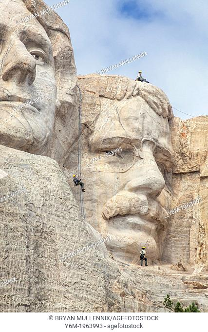 Park service employees rappel down the face of Mount Rushmore while conducting an inspection, Mount Rushmore National Monument, South Dakota