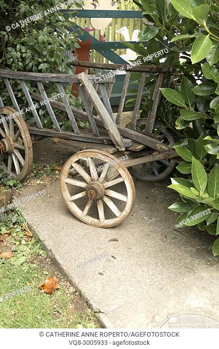 Old fashioned, weathered 'haywain' child's pull-along garden toy parked in the shrubbery by a garden gate in Frampton on Severn, the Cotswolds, England