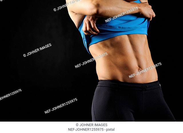 Woman with muscular torso taking off shirt