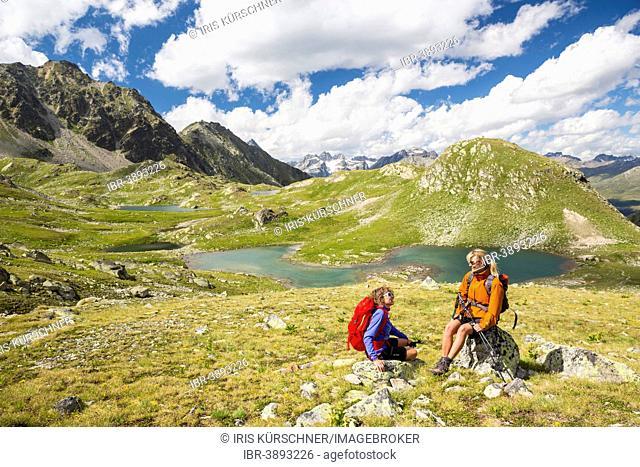 Two women hiking, resting at Macun lake plateau, views to Verstancla group and Silvretta group, Swiss National Park, Graubünden, Switzerland