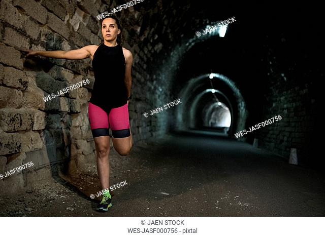 Sportive woman stretching in a tunnel